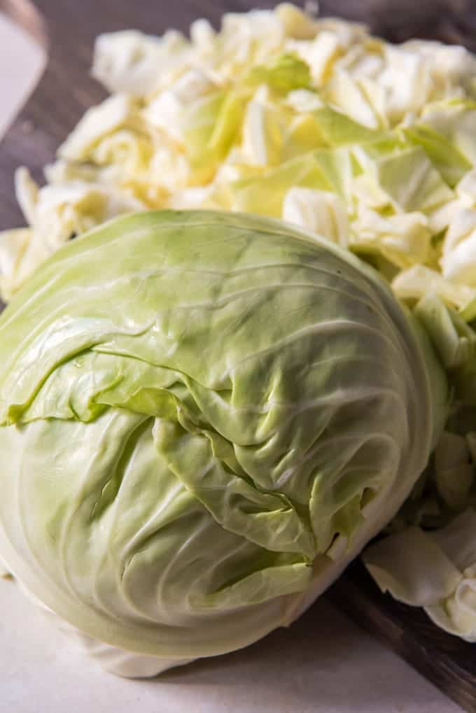 A head of cabbage on a cutting board, ready to be chopped for Irish colcannon, a traditional Irish food.