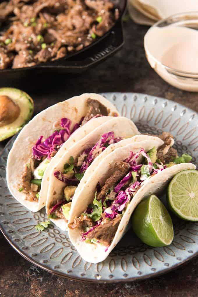 Three Korean Beef Tacos made with tender bulgogi beef and served on flour tortillas with purple cabbage, taco sauce, and avocados.