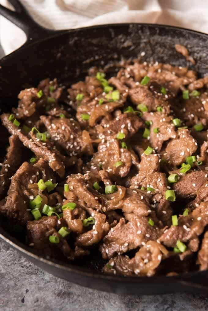 A large cast iron skillet filled with Korean bulgogi beef, topped with chopped green onions and sesame seeds.
