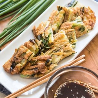 This recipe for Korean Pancakes (called Pajeon or Pa Jun) with Scallions and Dipping Sauce is wonderful for a snack, appetizer or light lunch.  The tender scallions impart a fresh, mild bite without making the pancake too onion-y, and the slightly sweet and savory dipping sauce is the perfect compliment to the crispy, fried pancake.