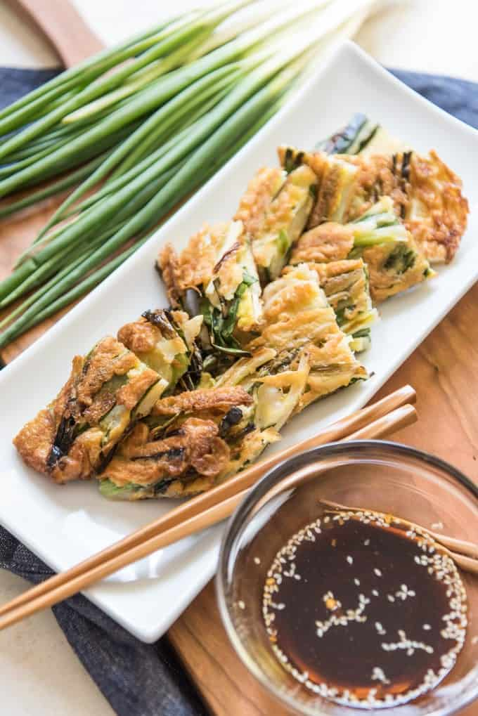 a white plate with korean scallion pancakes next to a bowl of sauce and fresh scallions