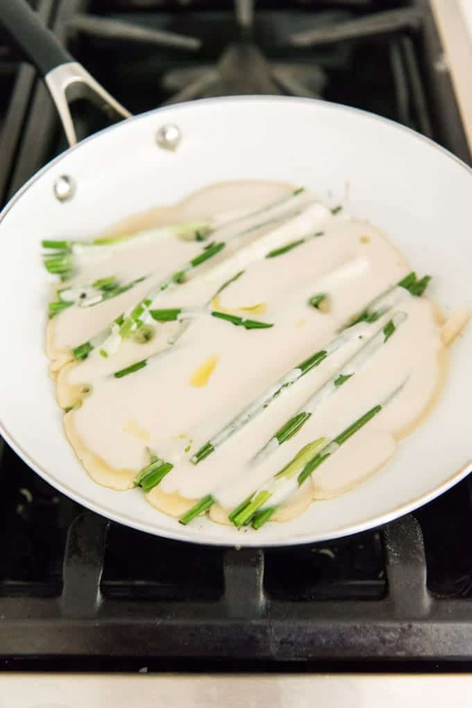 A non-stick pan on a stove with the batter cooking for a crispy Korean pancake with scallions in it.