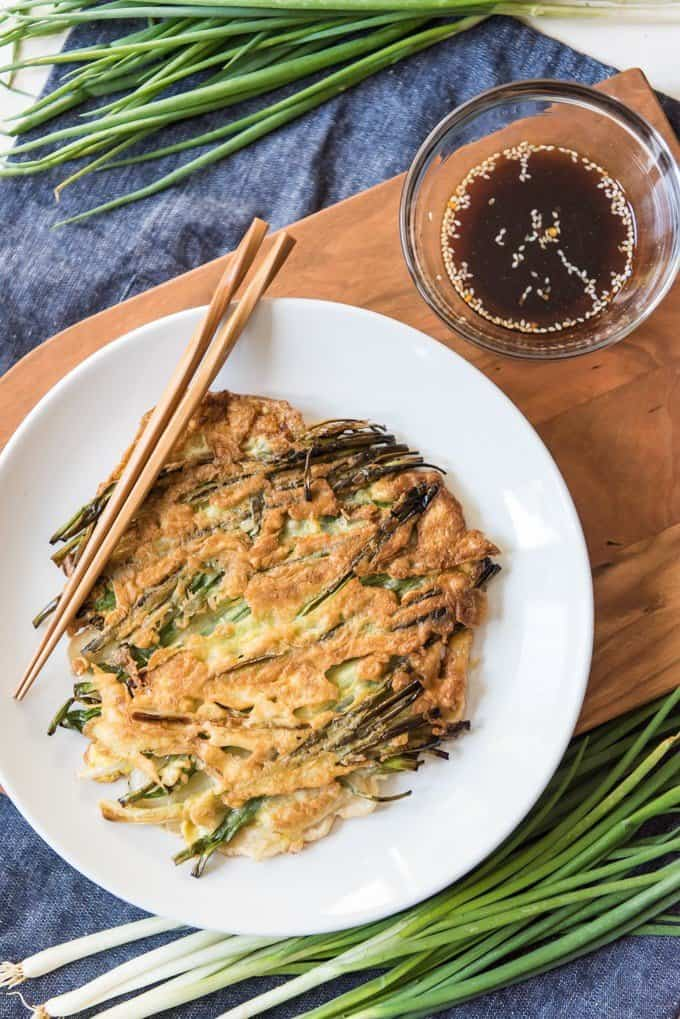 A full, round crispy Korean pancake (Pajeon or Pa Jun) made with scallions and served with a dipping sauce.