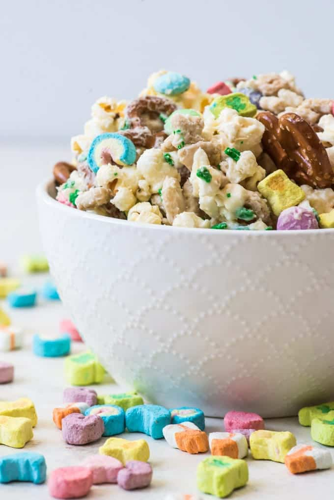 A bowl of Lucky Charms cereal mix with Lucky Charms marshmallows sprinkled around it.