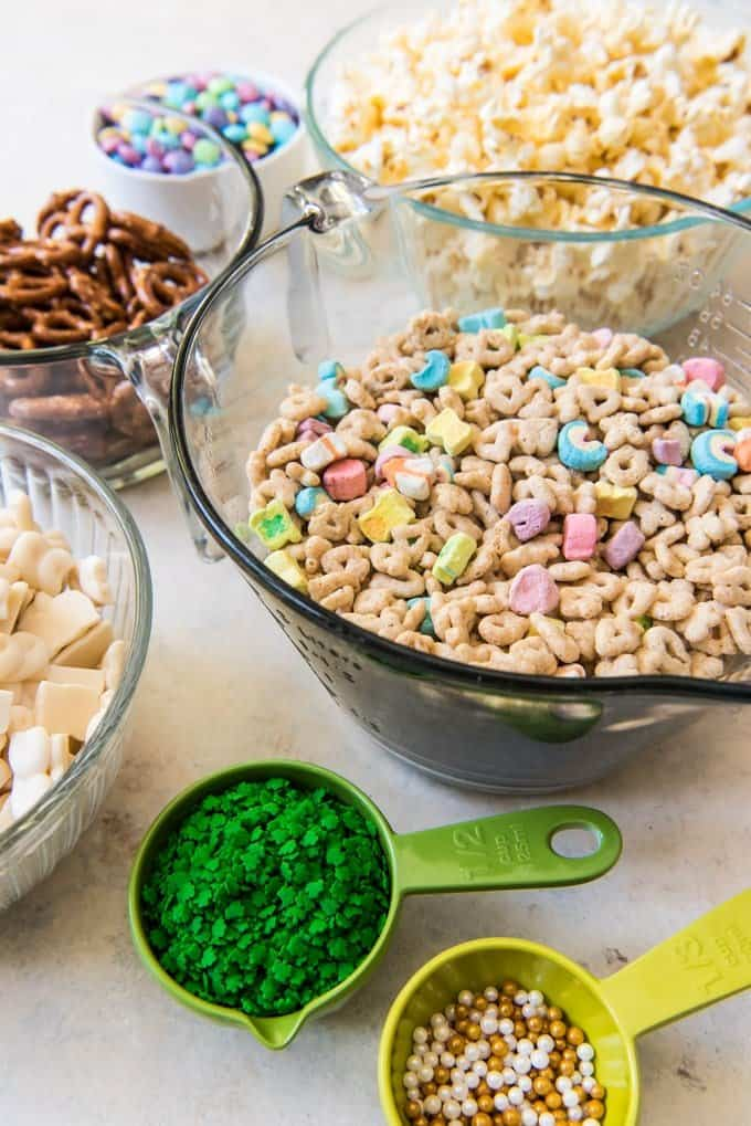 Ingredients in separate bowls for Lucky Charms Snack Mix in separate bowls.