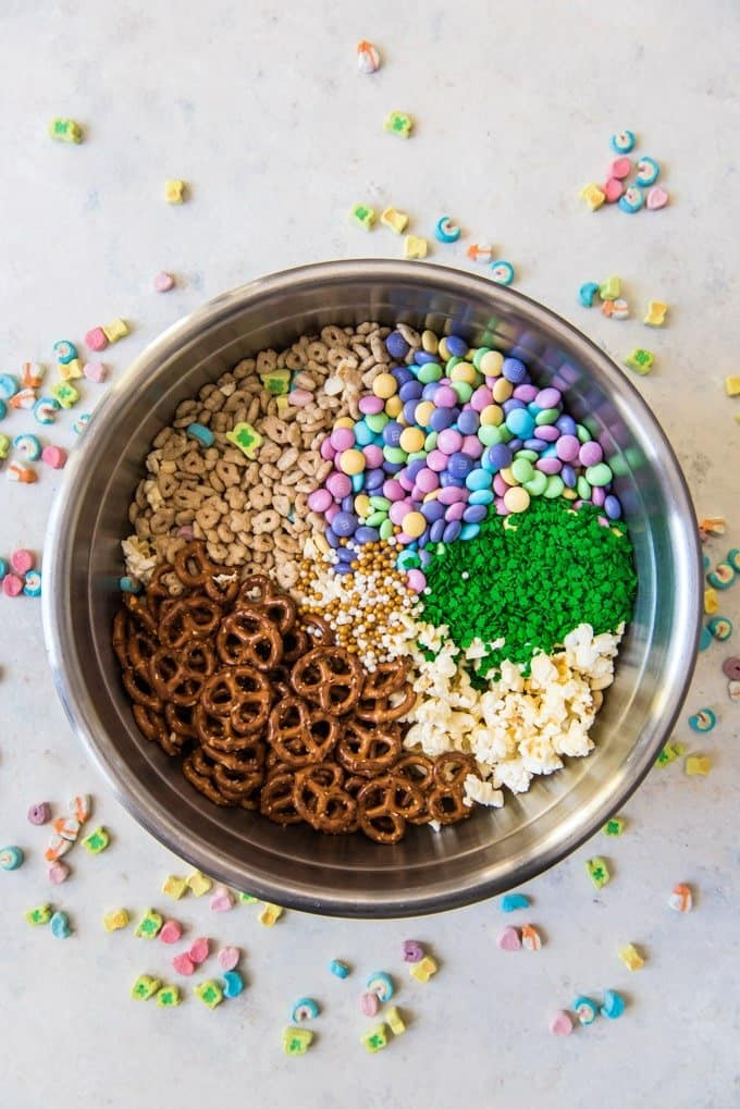All of the ingredients for Lucky Charms snack mix in a big silver bowl, ready to be mixed.