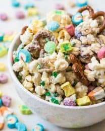 A bowl of Lucky Charms snack mix with pretzels, popcorn, lucky charms cereal, M&M's, and white chocolate.