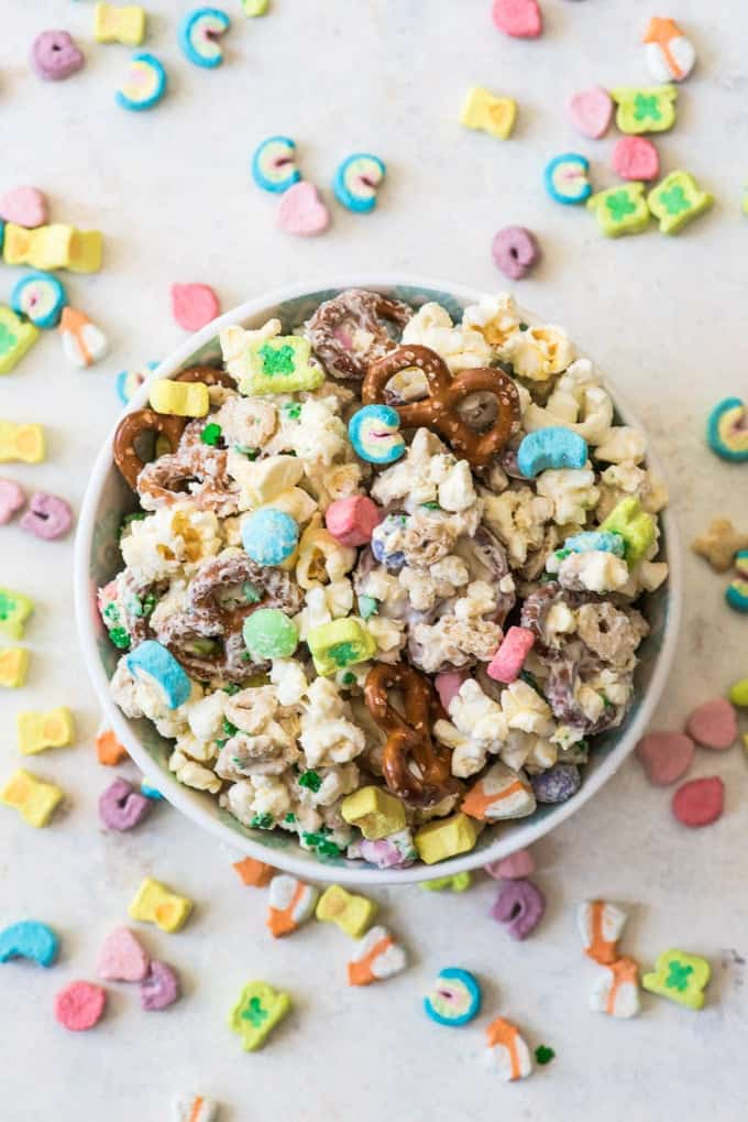 A bowl of leprechaun bait made with pretzels, popcorn, Lucky Charms cereal, white chocolate, and sprinkles.