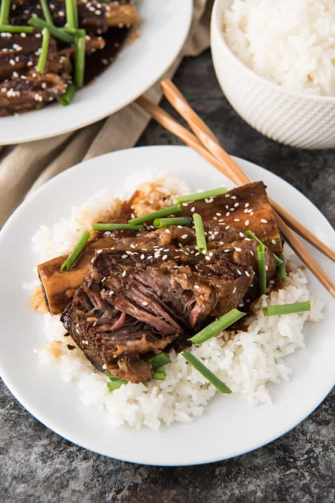 One braised beef short rib on a bed of white rice.