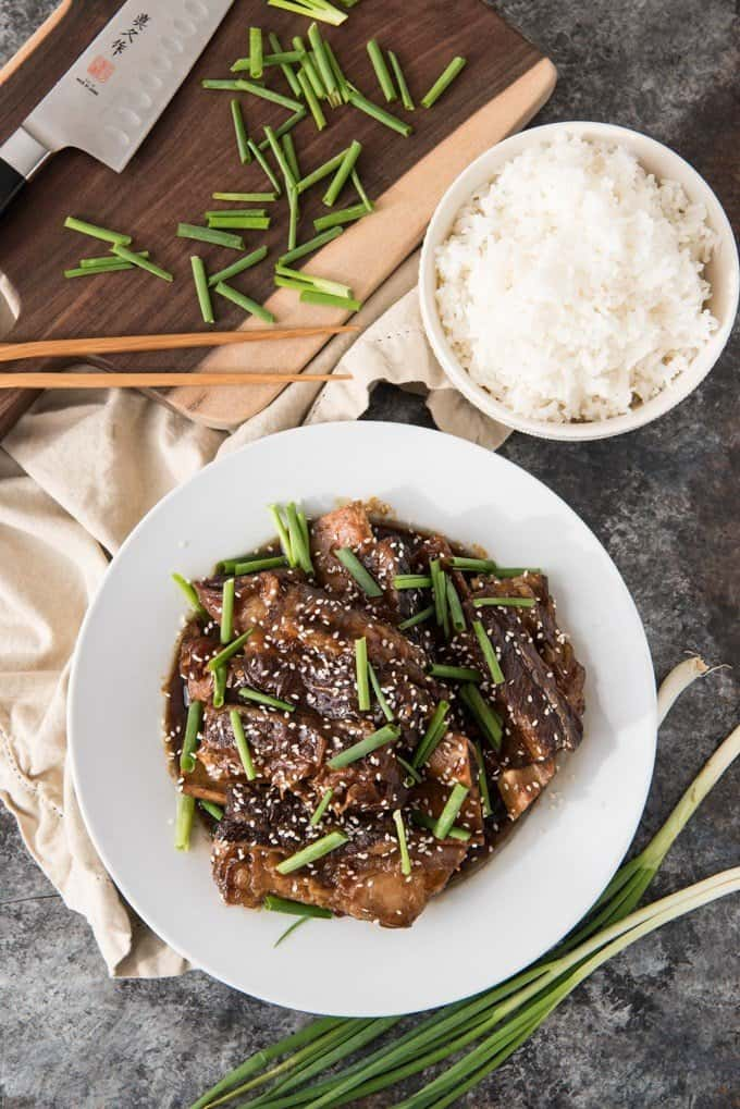 Overhead shot of slow cooker Korean beef short ribs on a white plate, garnished with chopped green onions, sesame seeds, and a bowl of white rice on the side.