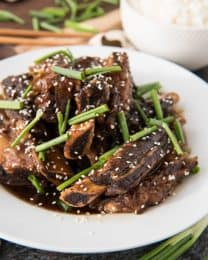 korean beef shortribs topped with sesame seeds and green onion on a white plate with a bowl of rice to the side