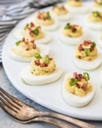 bacon and green onion deviled eggs on a serving platter with two forks to the side