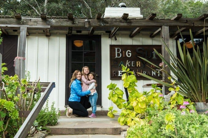 An image of a mother and daughters in front of a sign at the Big Sur Bakery and Restaurant.