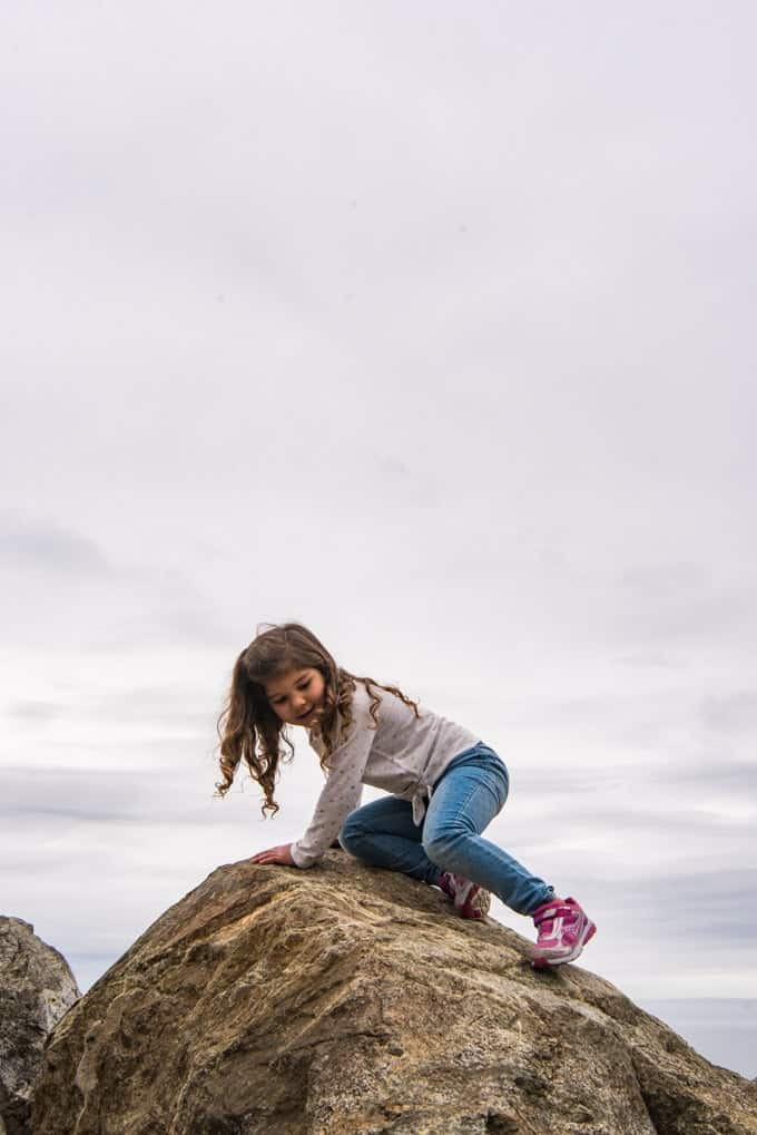 A young child climbing on a rock with expansive sky in the background.