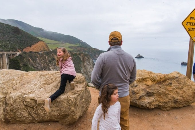 An image of a father looking at the ocean and a child climbing on rocks, with another child holding onto her father.