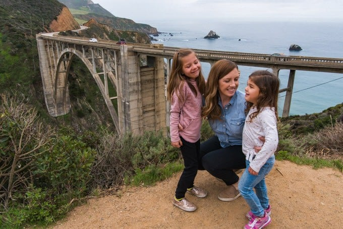 An image of a mother and two daughters at Bixy Bridge in Big Sur, California.