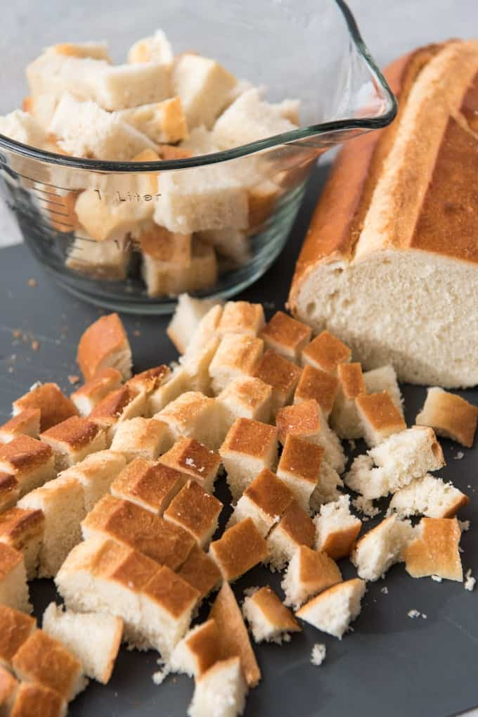 An image of a loaf of Italian bread cut into bite-size chunks to make croutons.