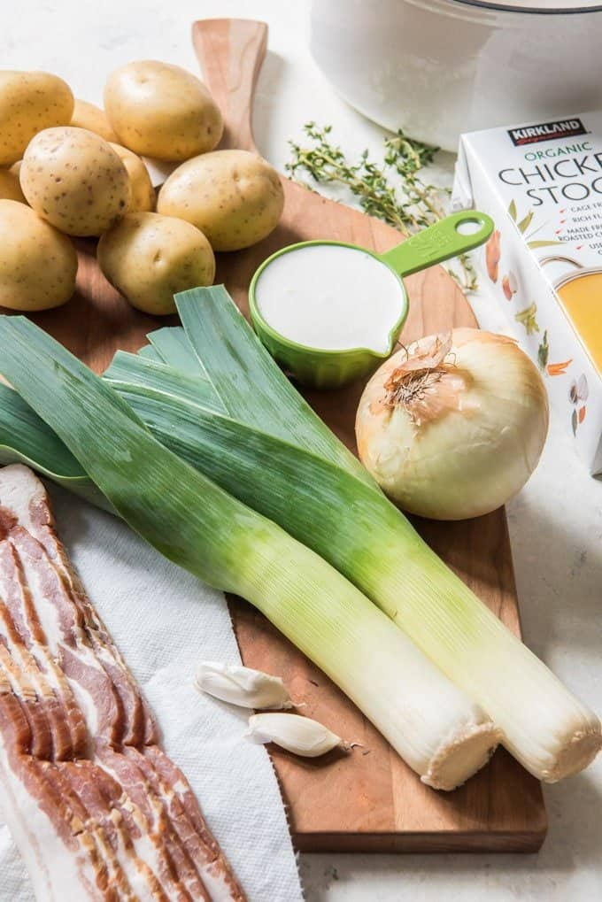 An image of two leeks, an onion, garlic, yellow potatoes, cream, and bacon on a wooden cutting board, ready to make potato leek soup.