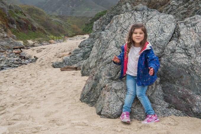 A child leaning against rocks on the beach at Garrapata State Park in Big Sur.