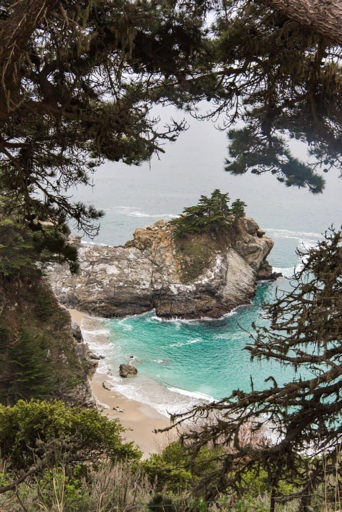 An image of a rocky outcropping in the Pacific Ocean at the cove of McWay Falls in Julia Pfeiffer Burns State Park.