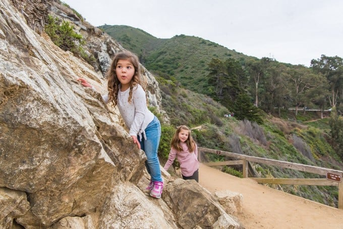 An image of a two young children climbing rocks along the McWay Waterfall Trail in Big Sur.