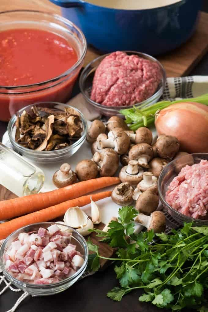 An image of all of the ingredients for the best bolognese sauce recipe, including ground beef, bround pork, pancetta, carrots, celery, onion, white wine, crushed tomatoes, mushrooms, and parsley.