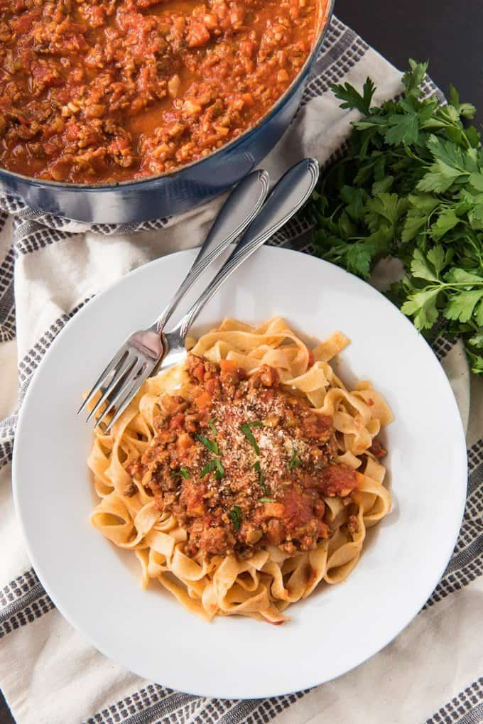 An image of a serving of bolognese sauce served over fresh tagliatelle pasta.