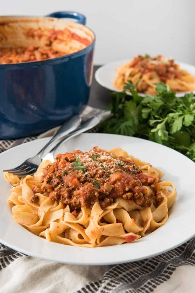 An image of a plate of tagliatella bolognese with a large dutch oven full of bolognese sauce behind.