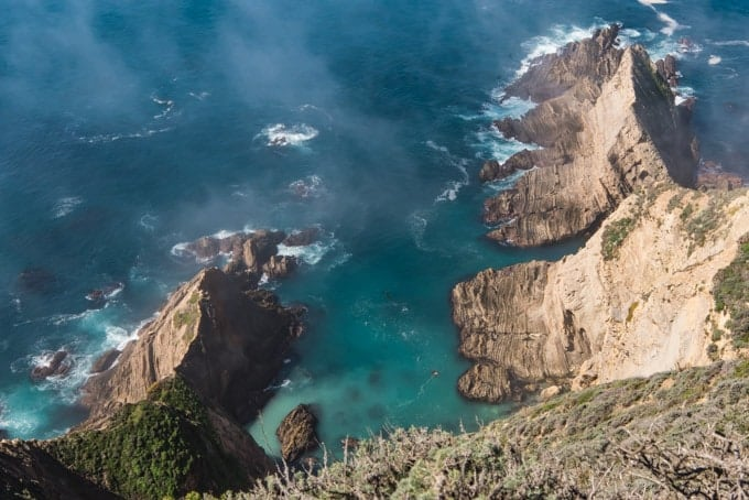 An image of rocky promontories from a high vantage point with turqoise water at Big Sur, California.