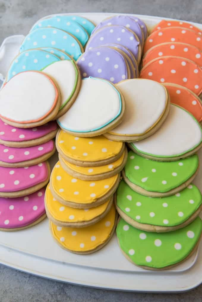 Dozens of sugar cookies with a simple polka dot design, stacked and ready for transport.