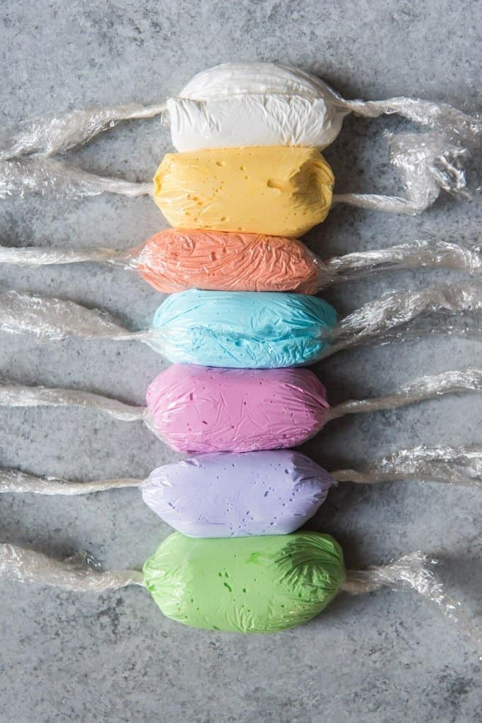 An image of 7 different colors of royal icing, each wrapped in a pouch of plastic wrap for inserting into a disposable piping bag.