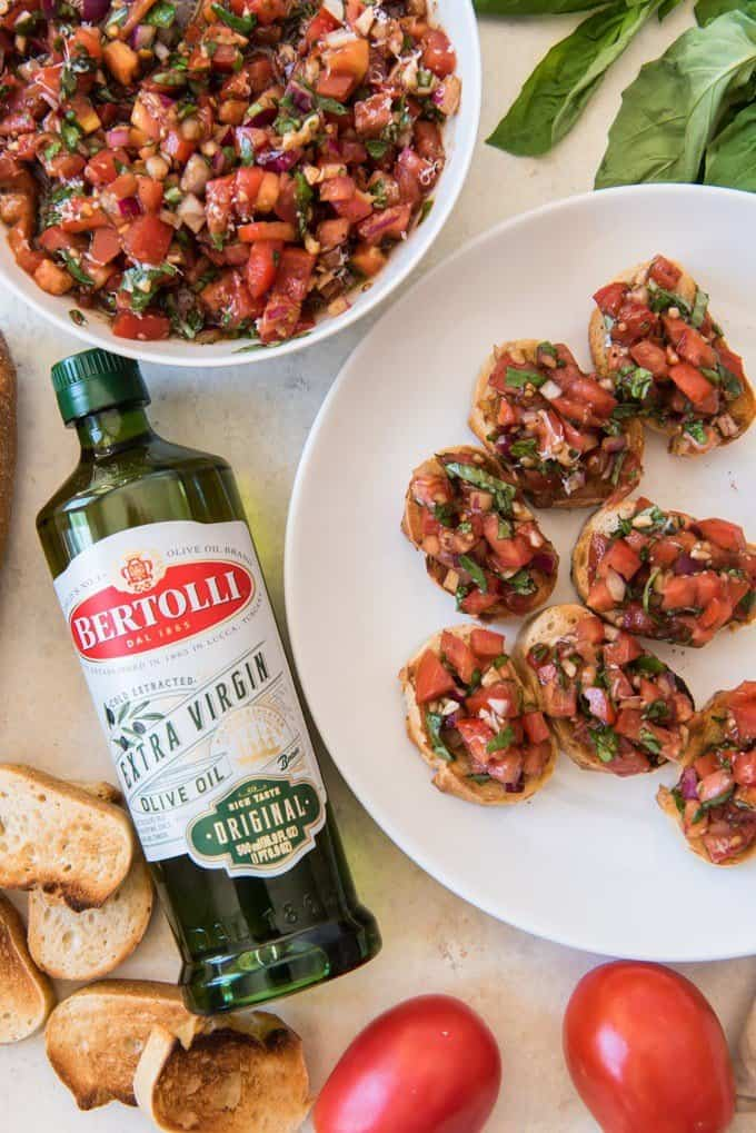An image of classic tomato basil bruschetta on individual toasts with a large bowl of the bruschetta filling next to some small toast rounds.