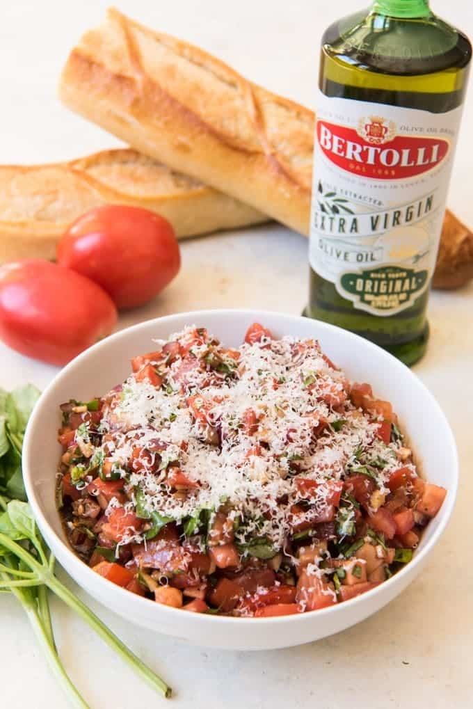 A large white bowl full of diced tomatoes, garlic, and fresh basil for a classic tomato basil bruschetta, with a sliced baguette and bottle of olive oil in the background.