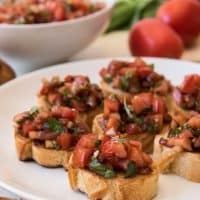 Small rounds of toasted baguette arranged on a white plate and topped with homemade Italian bruschetta.