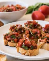 This classic bruschetta recipe uses fresh roma tomatoes, basil, garlic, a little balsamic vinegar, and Bertolli® Extra Virgin Olive Oil to top slices of toasted baguette.  It's easy, fresh, and makes a wonderful appetizer for any party or gathering!