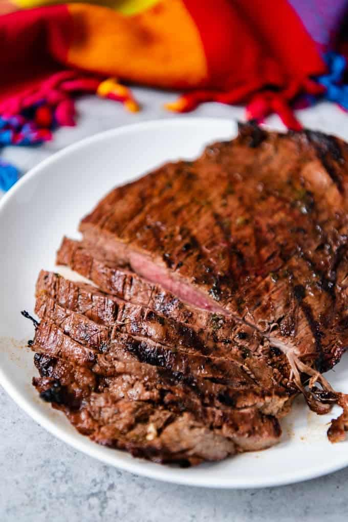 An image of a white plate of thinly sliced flank steak marinated in citrus juices, oil, chilies, spices, and cilantro and grilled for carne asada tacos.
