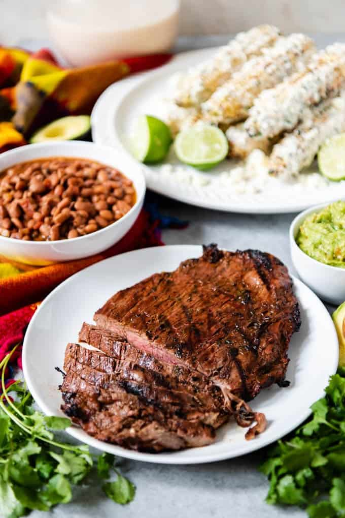 An image of a plate of grilled flank stead made with a quick and easy carne asada recipe, with mexican pinto beans and mexican street corn on the side.