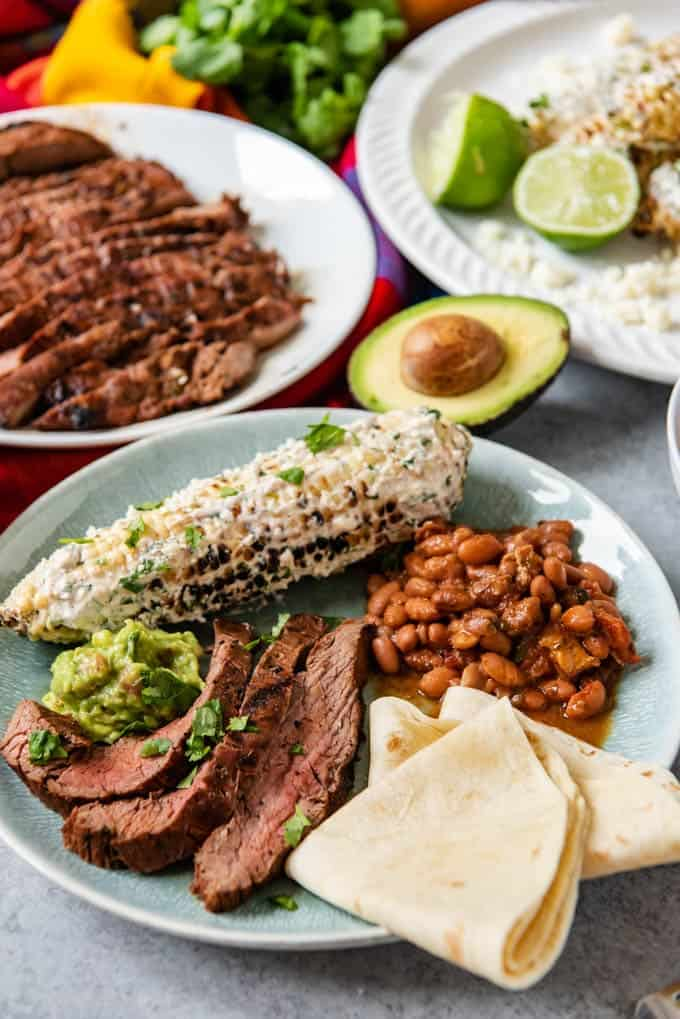 An image of a plate of grilled carne asada with charro beans, mexican street corn, guacamole, and soft flour tortillas.