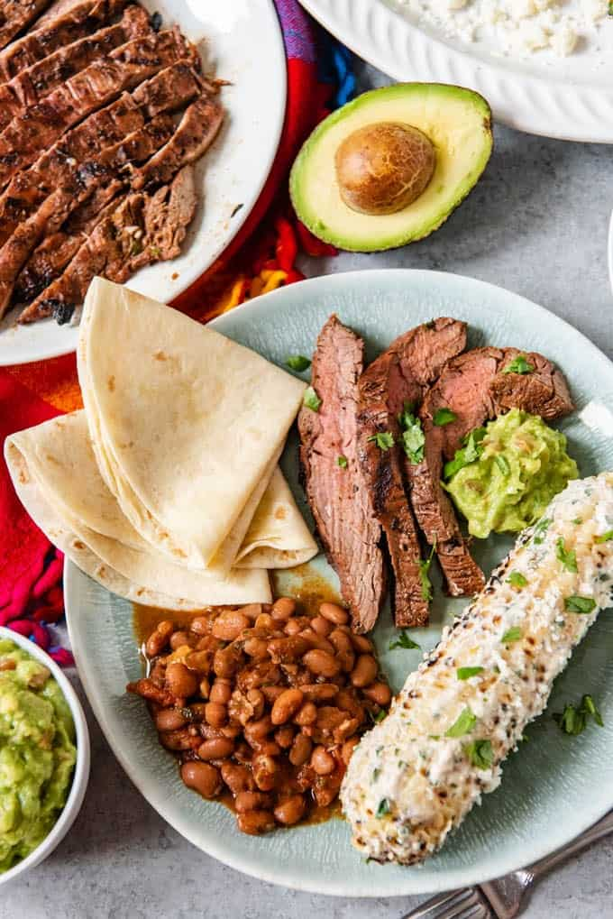 An image with a full mexican dinner for cinco de mayo with charro beans, flour tortillas, grilled Mexican street corn, and carne asada sliced into thin strips.