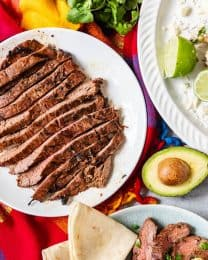 sliced carne asada on a white plate next to a halved avocado, tortillas, and more