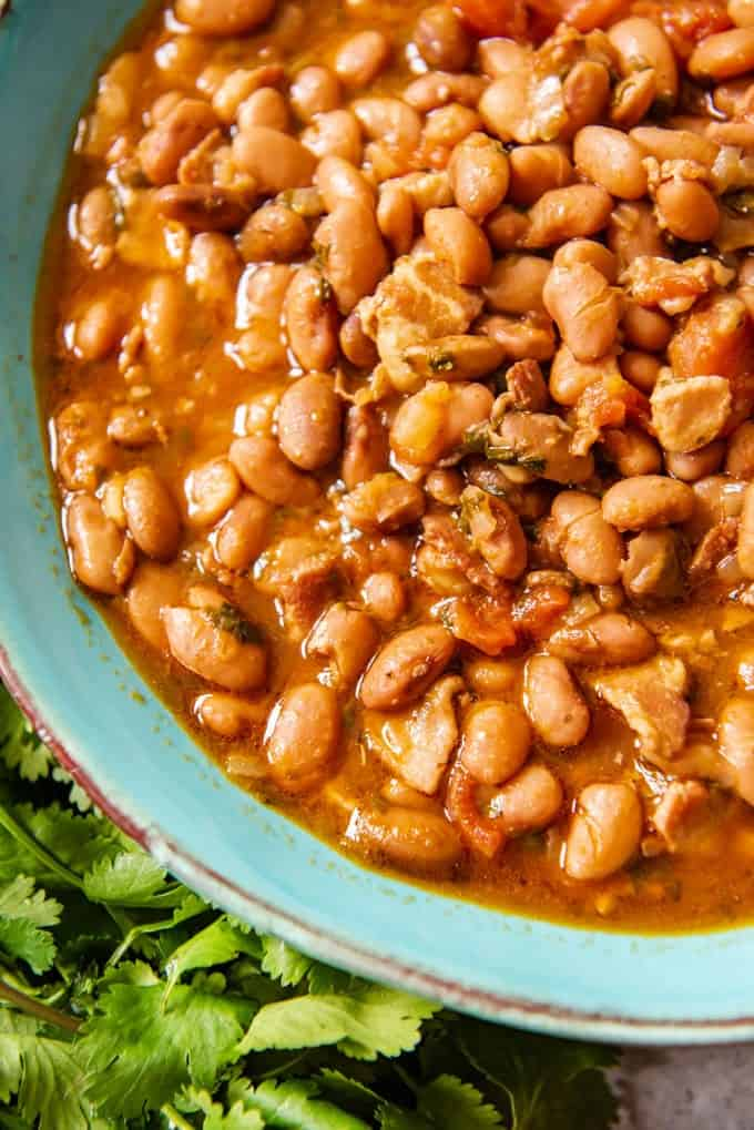 An image of a blue bowl full of pressure cooker charro beans (also known as frijoles charros or cowboy beans).