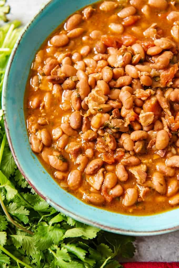 An image of a blue bowl full of charro beans (also known as frijoles charros or cowboy beans) made in a pressure cooker.