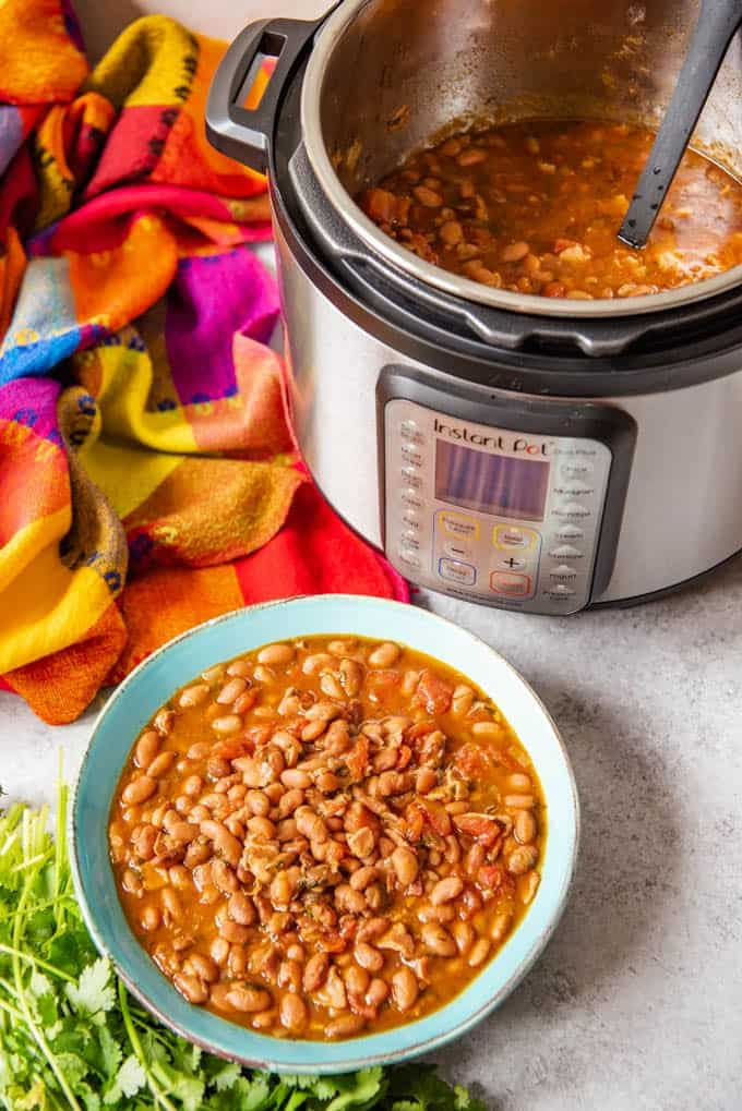 An image of a bowl of Mexican pressure cooker pinto beans called charro beans in front of an Instant Pot.