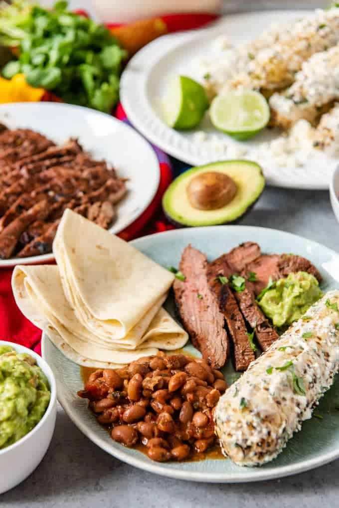 An image of a Cinco de Mayo Mexican fiest, perfect for a fiesta with fresh tortillas, charro beans, carne asada, guacamole, grilled Mexican street corn, and horchata!