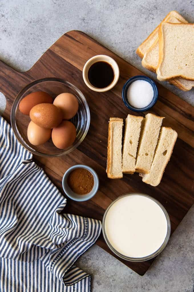 An image of the ingredients for making french toast sticks, including eggs, cream, cinnamon, vanilla, sugar, and stale texas toast.