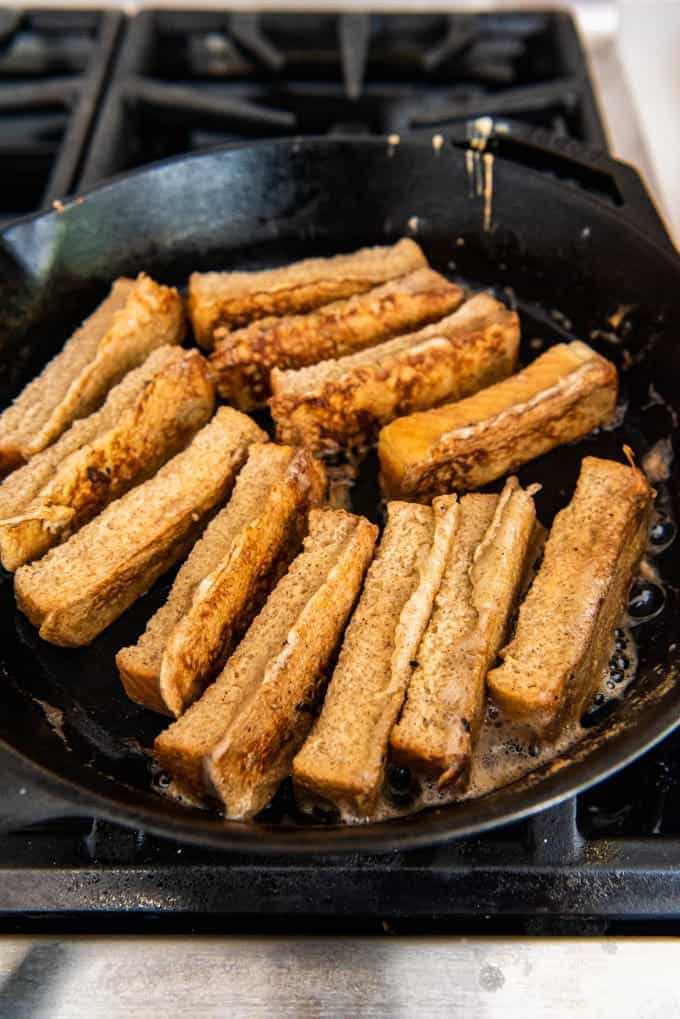 An image of french toast sticks frying in butter in a pan.