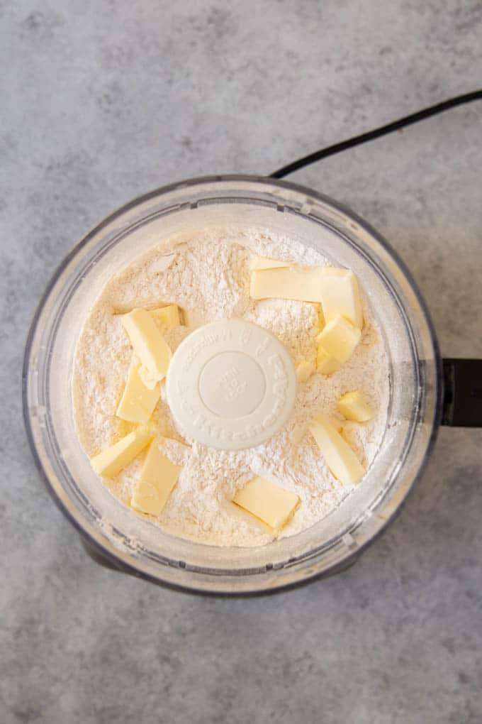 An image of cubed butter in the bowl of a food processor with flour and sugar for a sweet pastry crust for a French tart.