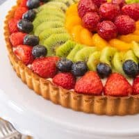 a fresh and colorful french fruit tart on a white cakestand