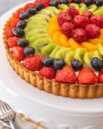 Fresh, colorful, and bursting with juicy fruit, rich pastry cream, a deliciously sweet pastry crust, and an easy fruit tart glaze, this French fruit tart recipe makes a showstopper dessert that is perfect for Spring & Summer!