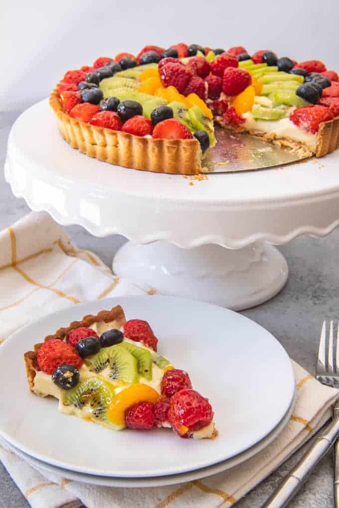 An image of a fresh fruit tart on a white cake stand, with one slice cut and served on a white plate.